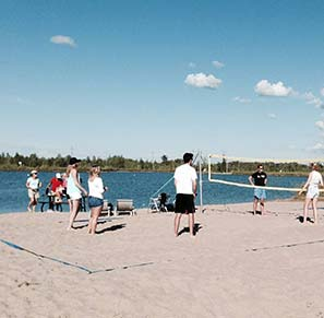 members playing beach volleyball at the new pond