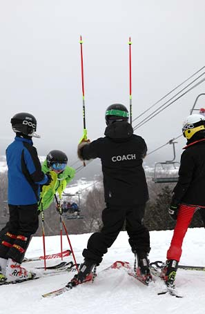 ski coach teaching kids on hill