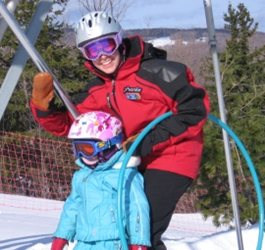 Smiling ski instructor teaching child to ski