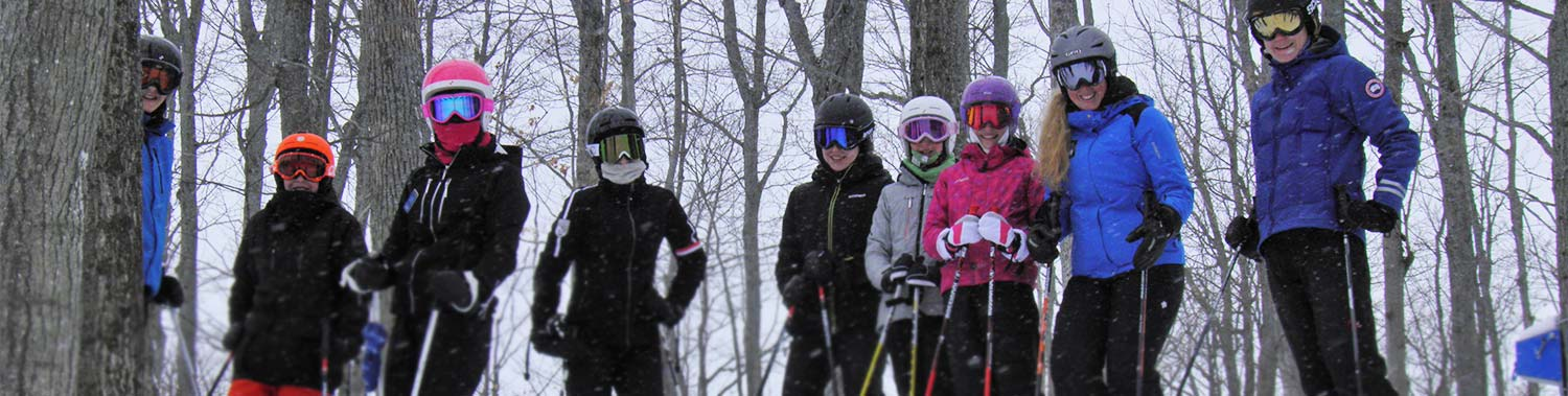snow school instructor on hill with students